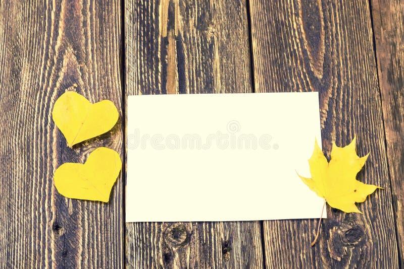 Καρδιές από τα κίτρινα φύλλα φθινοπώρου και ένα κενό φύλλο του εγγράφου στοκ εικόνες