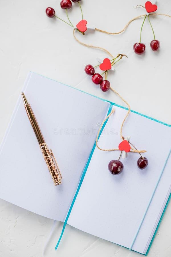 Καρδιές και κεράσι Να ονειρευτεί θέμα για την αγάπη Ένα ανοικτό σημειωματάριο είναι σε ένα άσπρο υπόβαθρο ξύλινη κόκκινη καρδιά,  στοκ φωτογραφία