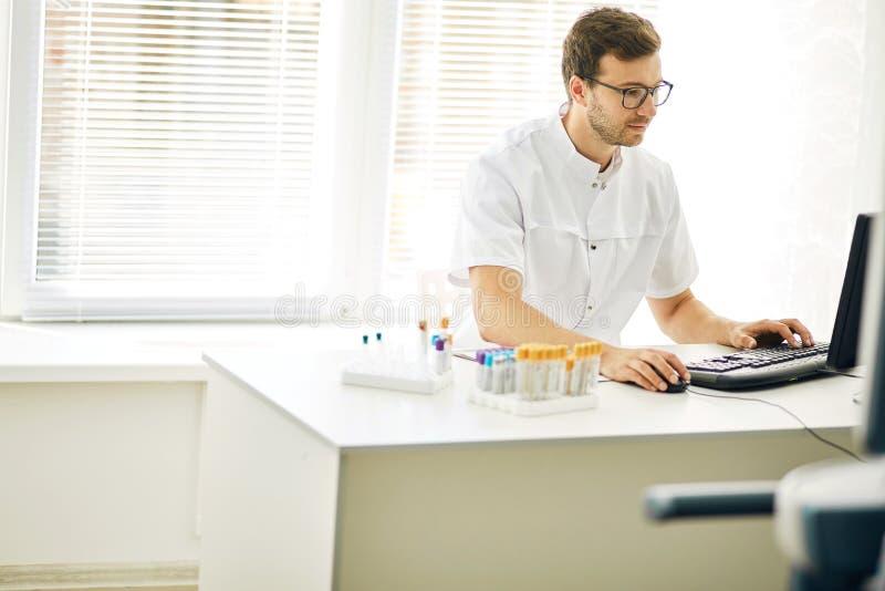 Καρδιολόγος που χρησιμοποιεί το lap-top στο γραφείο θολωμένο ανασκόπηση χάπι μασκών υγείας προσώπου έννοιας προσοχής προστατευτικ στοκ φωτογραφία με δικαίωμα ελεύθερης χρήσης