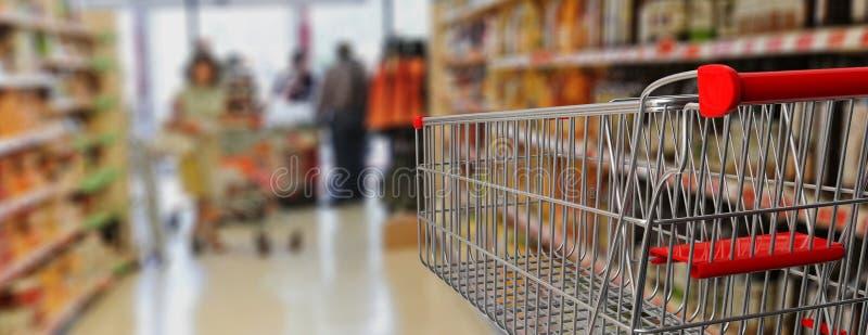 Καροτσάκι αγορών, κενό, με την κόκκινη λαβή στο υπόβαθρο υπεραγορών θαμπάδων τρισδιάστατη απεικόνιση ελεύθερη απεικόνιση δικαιώματος