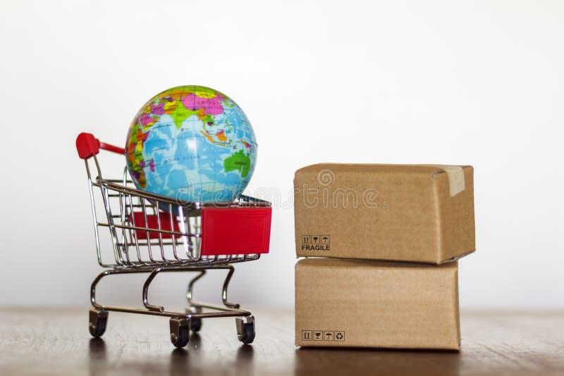 Καροτσάκι αγορών με τη σφαίρα χαρτοκιβωτίων και γης Διεθνείς αγορές και σφαιρική έννοια διοικητικών μεριμνών στοκ φωτογραφίες με δικαίωμα ελεύθερης χρήσης