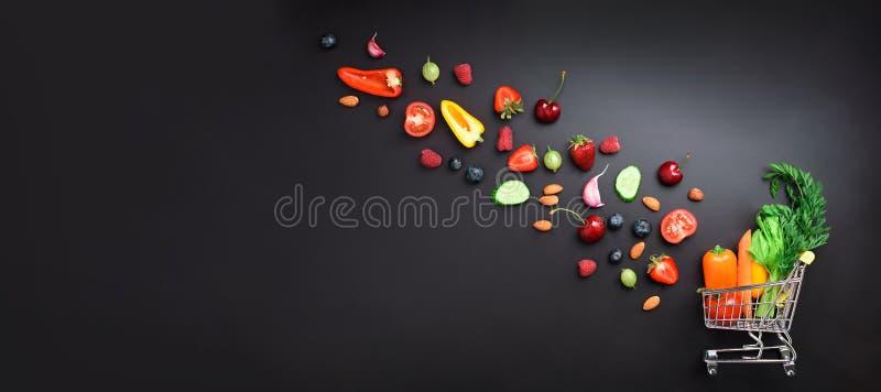Καροτσάκι αγορών που γεμίζουν με τα φρέσκα οργανικά λαχανικά, τα φρούτα και τα μούρα στο μαύρο πίνακα κιμωλίας Τοπ όψη χορτοφάγος στοκ εικόνα με δικαίωμα ελεύθερης χρήσης