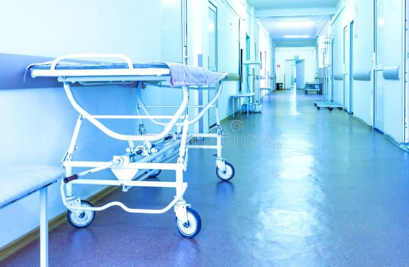 Καροτσάκι για τους ασθενείς σε έναν μακρύ διάδρομο του σύγχρονου νοσοκομείου Χειρουργικό τμήμα Μπλε τονισμός στοκ φωτογραφία