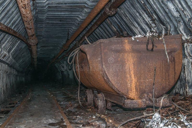 Καροτσάκι στη σήραγγα ορυχείων με τις ράγες στοκ φωτογραφία