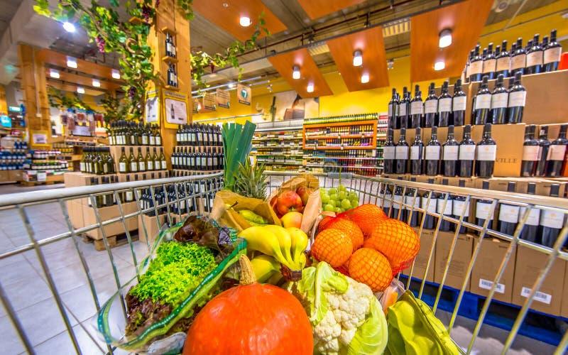 Καροτσάκι υπεραγορών με τα φρούτα και λαχανικά στο τμήμα κρασιού στοκ εικόνα