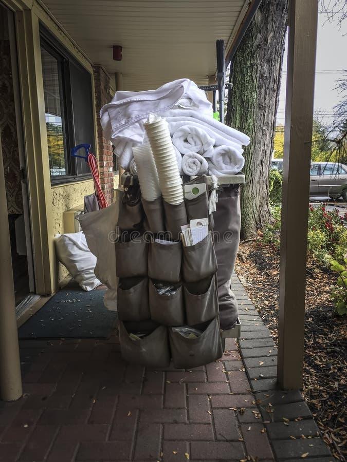 Καροτσάκι υπηρεσιών ξενοδοχείων που φορτώνεται με τις πετσέτες και τον καθαρίζοντας εξοπλισμό στοκ εικόνες