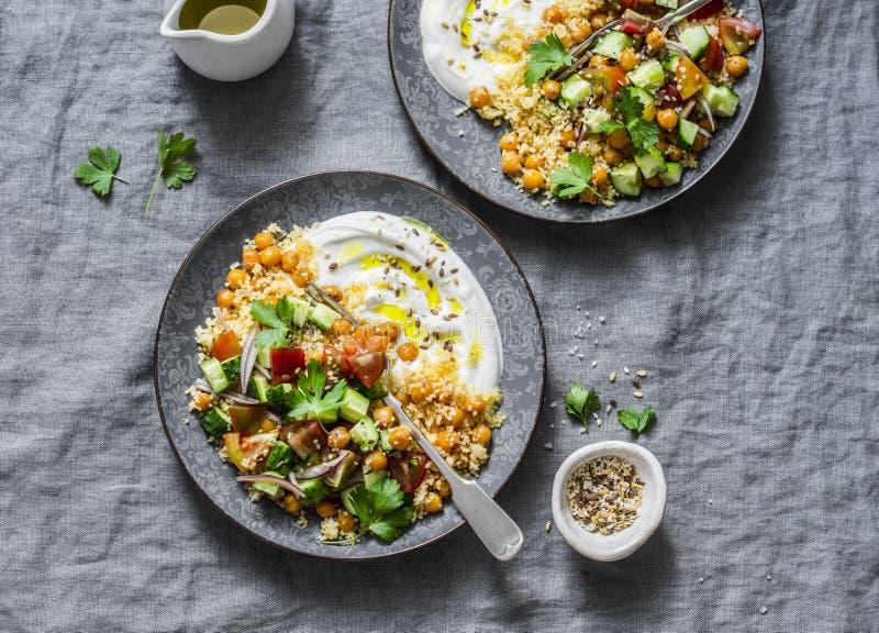 Καρυκευμένα chickpeas και κουσκούς με τη σαλάτα ποιμένων ` s και το ελληνικό γιαούρτι σε ένα γκρίζο υπόβαθρο, τοπ άποψη στοκ εικόνες