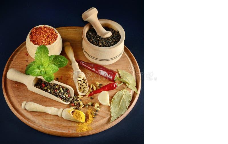 Καρυκεύματα και φυστίκια ποικιλίας στα ξύλινα κουτάλια και φλυτζάνια στο μαύρο BA στοκ εικόνα με δικαίωμα ελεύθερης χρήσης