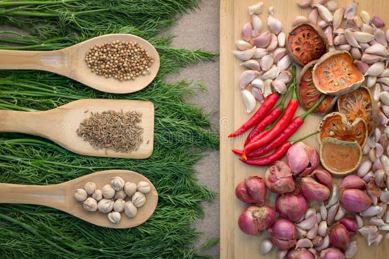 Καρυκεύματα και χορτάρια με τα ξύλινα τρόφιμα κύπελλων κουταλιών και το ingredi κουζίνας στοκ φωτογραφία με δικαίωμα ελεύθερης χρήσης
