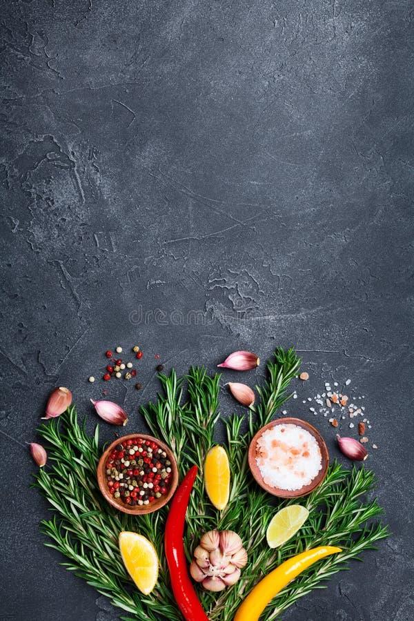 Καρυκεύματα και χορτάρια στη μαύρη άποψη επιτραπέζιων κορυφών πετρών Συστατικά για το μαγείρεμα τρόφιμα μπουλεττών ανασκόπησης πο στοκ φωτογραφίες