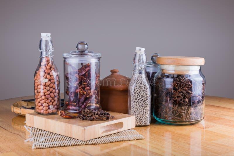 καρυκεύματα στα μπουκάλια γυαλιού στο ξύλινο υπόβαθρο στοκ φωτογραφία με δικαίωμα ελεύθερης χρήσης