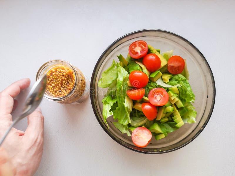 Καρυκεύοντας για τη φυτική σαλάτα, που προσθέτει τη γαλλική μουστάρδα στη φυτική σαλάτα, τρόφιμα Vigatarian, υγιή τρόφιμα Θηλυκή  στοκ φωτογραφία