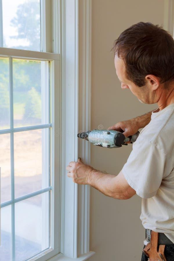 Καρφί ξυλουργών που χρησιμοποιεί το πυροβόλο όπλο καρφιών στις σχηματοποιήσεις στα παράθυρα, που πλαισιώνουν την περιποίηση, στοκ φωτογραφία