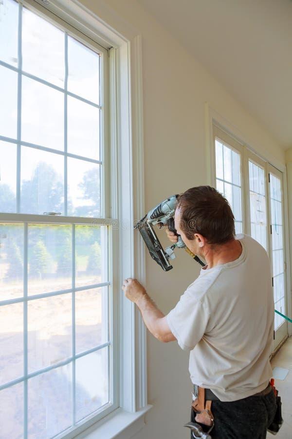 Καρφί ξυλουργών που χρησιμοποιεί το πυροβόλο όπλο καρφιών στις σχηματοποιήσεις στα παράθυρα, που πλαισιώνουν την περιποίηση, στοκ φωτογραφίες
