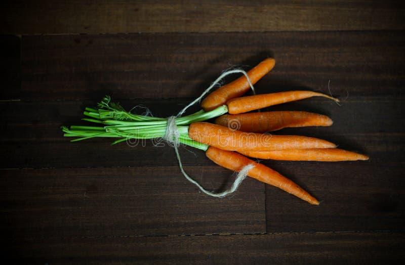 Καρότα με τα πράσινα, που δένονται στο καφετί ξύλο στοκ εικόνα με δικαίωμα ελεύθερης χρήσης