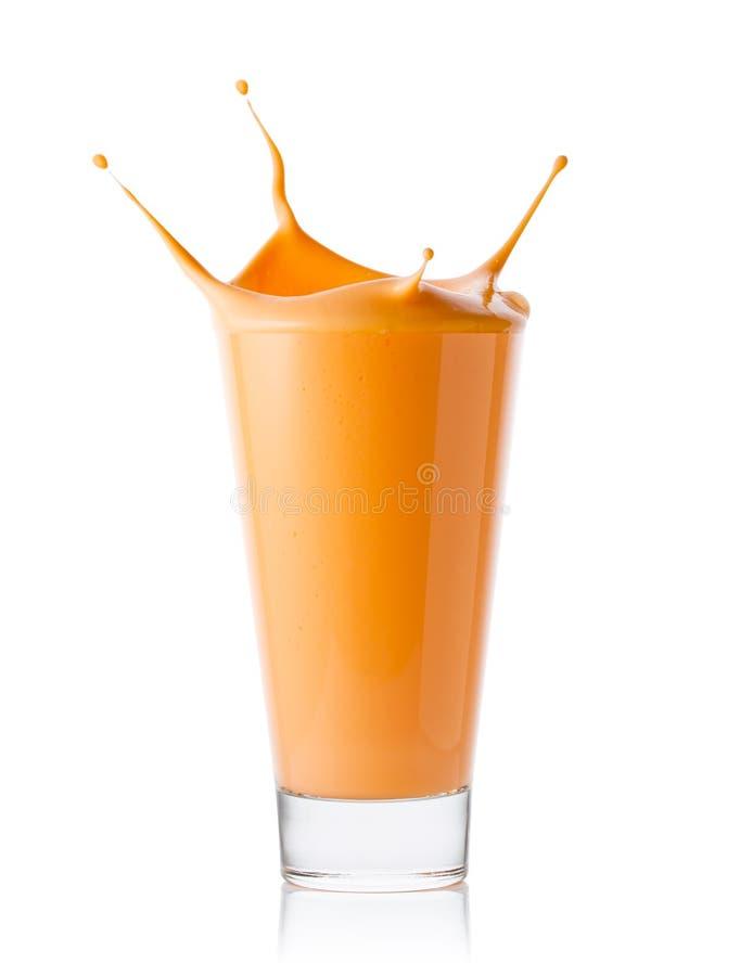 Καρότο ή καταφερτζής ή γιαούρτι εσπεριδοειδών με τον παφλασμό στο γυαλί στοκ φωτογραφία