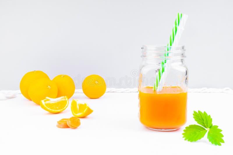 καρότο και χυμό πορτοκάλι με πράσινο φύλλο στοκ εικόνα