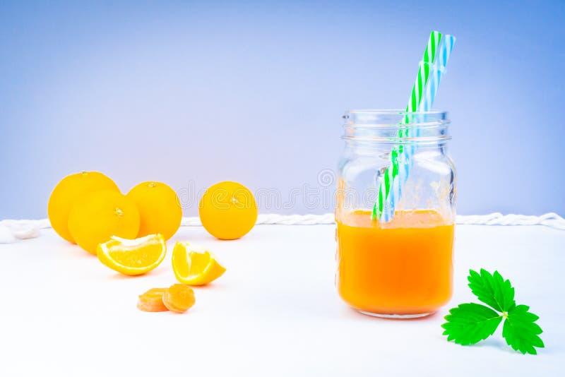 καρότο και χυμό πορτοκάλι με πράσινο φύλλο στοκ φωτογραφία