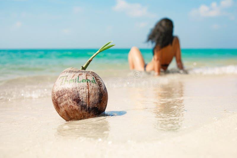 Καρύδα στο τροπικό νησί με το νέο κορίτσι στο μπικίνι στο backgrou στοκ φωτογραφία