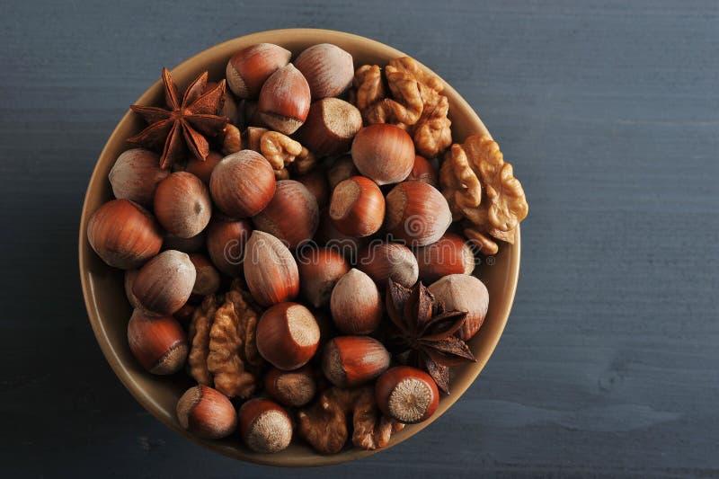 Καρύδια στο κύπελλο - φουντούκι στο κοχύλι, ξεφλουδισμένα ξύλα καρυδιάς, γλυκάνισο στοκ εικόνα με δικαίωμα ελεύθερης χρήσης