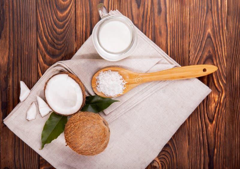 Καρύδες και κουτάλι με τα τσιπ καρυδιών σε ένα ύφασμα και ένα ξύλινο υπόβαθρο Γάλα καρύδων σε ένα βάζο κτιστών Υγιή και οργανικά  στοκ φωτογραφία με δικαίωμα ελεύθερης χρήσης