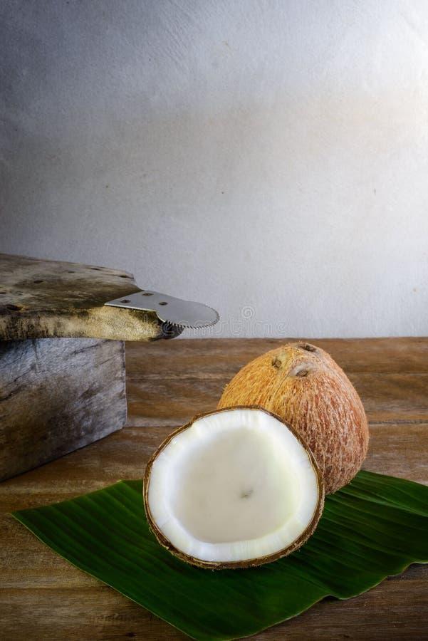 Καρύδες στο φύλλο μπανανών και τον ξύστη καρύδων στοκ εικόνα
