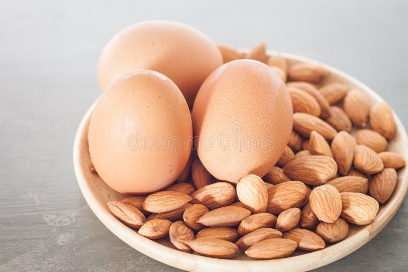Καρύδια και αυγά αμυγδάλων στο ξύλινο πιάτο στοκ φωτογραφία με δικαίωμα ελεύθερης χρήσης