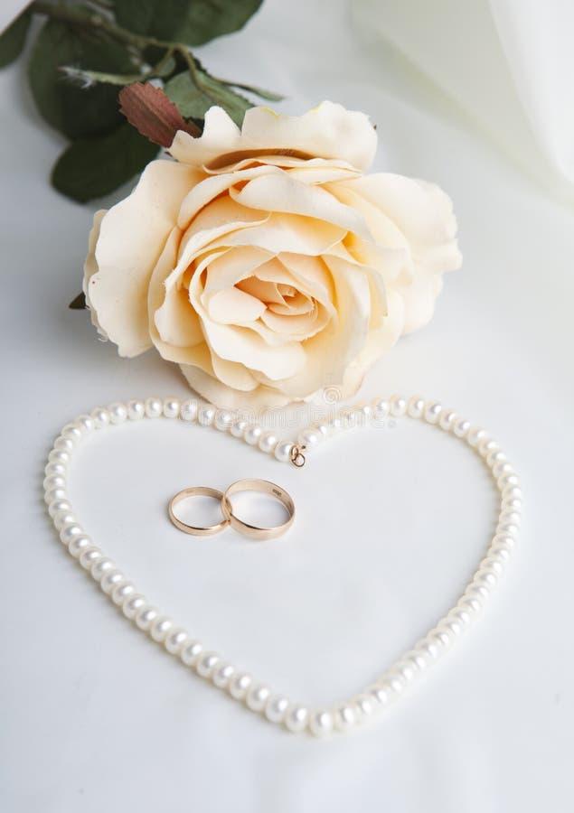Καρδιά μαργαριταριών, ένα τριαντάφυλλο και γαμήλια δαχτυλίδια στοκ φωτογραφία με δικαίωμα ελεύθερης χρήσης