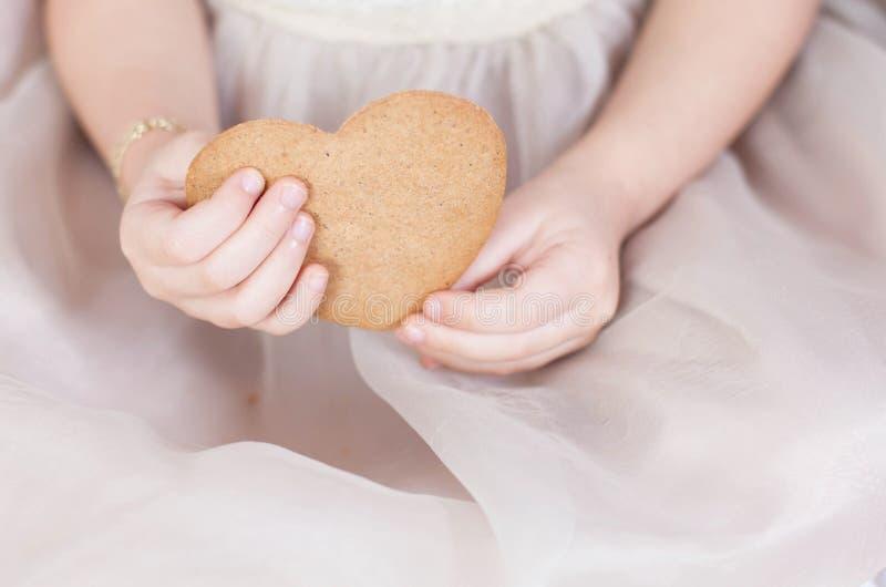 Καρδιά μελοψωμάτων στα χέρια ενός παιδιού στοκ φωτογραφία