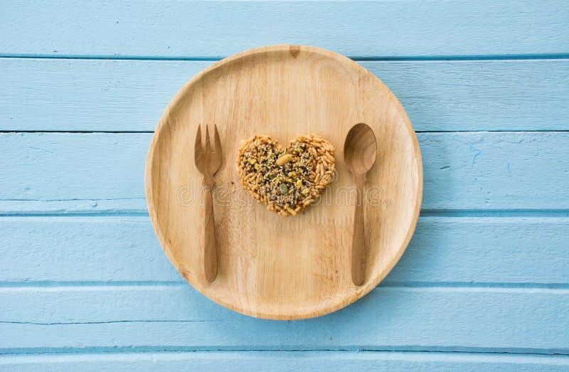 Καρδιά μορφής που γίνεται από ολόκληρο το σιτάρι στο ξύλινο πιάτο στοκ εικόνες
