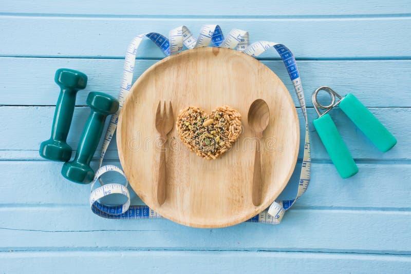 Καρδιά μορφής που γίνεται από ολόκληρο το σιτάρι στο ξύλινο πιάτο στοκ εικόνα
