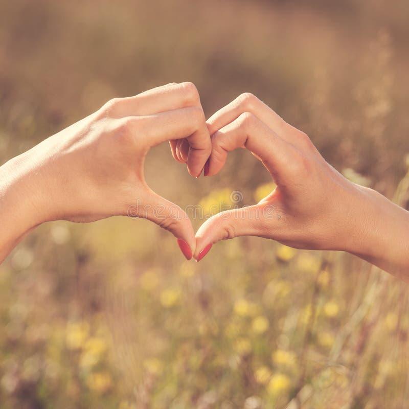 Καρδιά που γίνεται με τα δάχτυλα γυναικών στοκ εικόνα