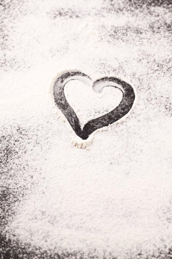Καρδιά που σύρεται στο διεσπαρμένο αλεύρι στοκ φωτογραφίες