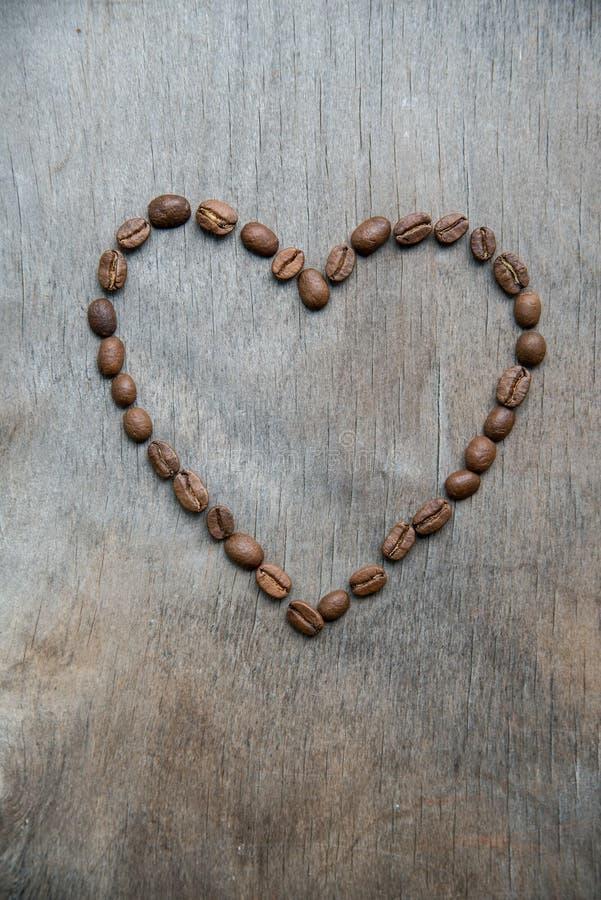 Καρδιά των φασολιών καφέ στο ξύλινο υπόβαθρο στοκ φωτογραφίες με δικαίωμα ελεύθερης χρήσης