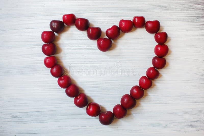 Καρδιά φιαγμένη από σκοτεινά κεράσια Κόκκινα φρούτα στο ξύλινο υπόβαθρο Το καλοκαίρι στέλνει την αγάπη Μόρια της τέχνης στοκ φωτογραφίες