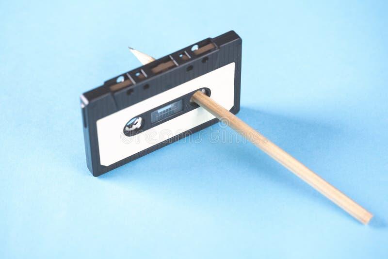 Κασέτα και μολύβια στο μπλε επιτραπέζιο υπόβαθρο στοκ εικόνα με δικαίωμα ελεύθερης χρήσης