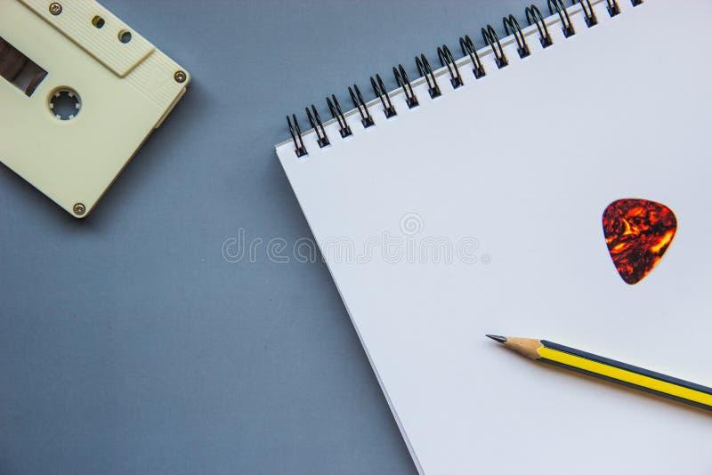 Κασέτα, μολύβι, επιλογή κιθάρων και κενό σημειωματάριο στο γκρίζο πάτωμα στοκ εικόνες