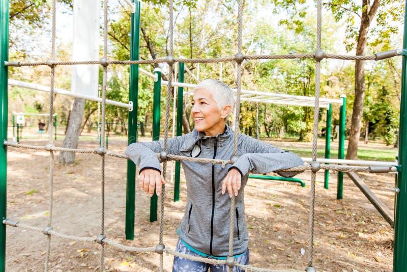 Κατάλληλη ανώτερη άσκηση γυναικών στην υπαίθρια γυμναστική στοκ φωτογραφία