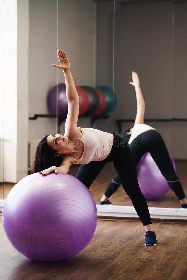 Κατάλληλη γυναίκα που κάνει pilates την άσκηση που χρησιμοποιεί τη σφαίρα στη γυμναστική στοκ φωτογραφίες με δικαίωμα ελεύθερης χρήσης
