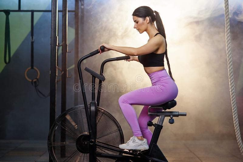 Κατάλληλη ελκυστική γυναίκα που επιλύει στο ποδήλατο άσκησης στη γυμναστική στοκ φωτογραφία