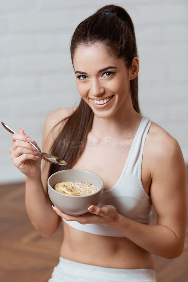 Κατάλληλη, ελκυστική γυναίκα που κρατά ένα κύπελλο oatmeal στοκ εικόνα με δικαίωμα ελεύθερης χρήσης