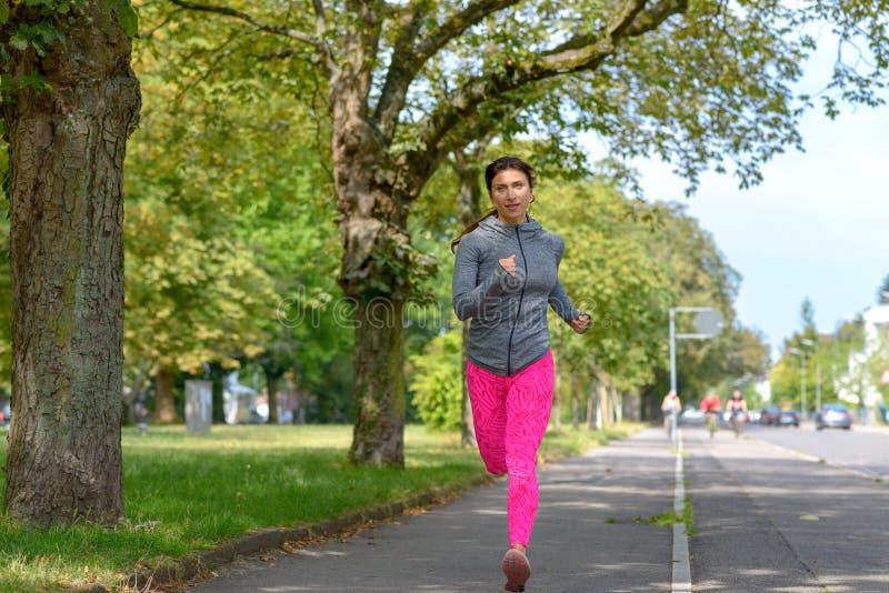 Κατάλληλη ενήλικη γυναίκα που τρέχει στο συγκεκριμένο πεζοδρόμιο στοκ φωτογραφία με δικαίωμα ελεύθερης χρήσης