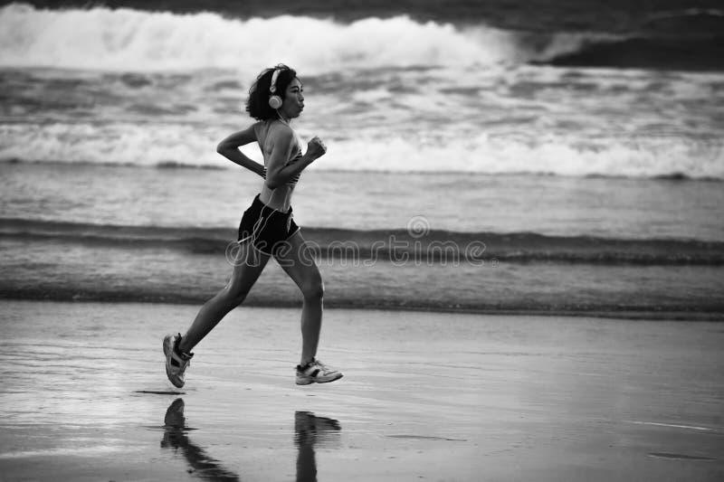 Κατάλληλη και αθλητική ασιατική κινεζική φίλαθλη γυναίκα που τρέχει στην όμορφη παραλία που κάνει workout στο ηλιοβασίλεμα στο υγ στοκ εικόνες