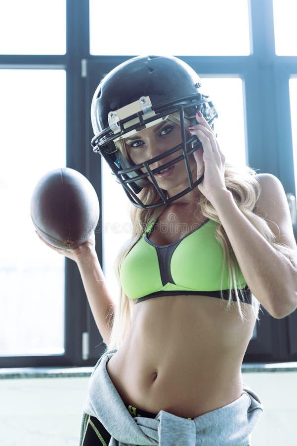 κατάλληλη νέα γυναίκα στον αθλητικό στηθόδεσμο και τη σφαίρα και το κοίταγμα εκμετάλλευσης κρανών αμερικανικού ποδοσφαίρου στοκ εικόνες