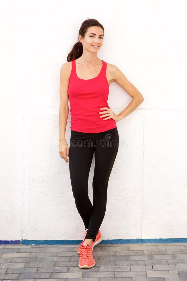 Κατάλληλη νέα γυναίκα sportswear που στέκεται με βεβαιότητα ενάντια στον άσπρο τοίχο στοκ εικόνα