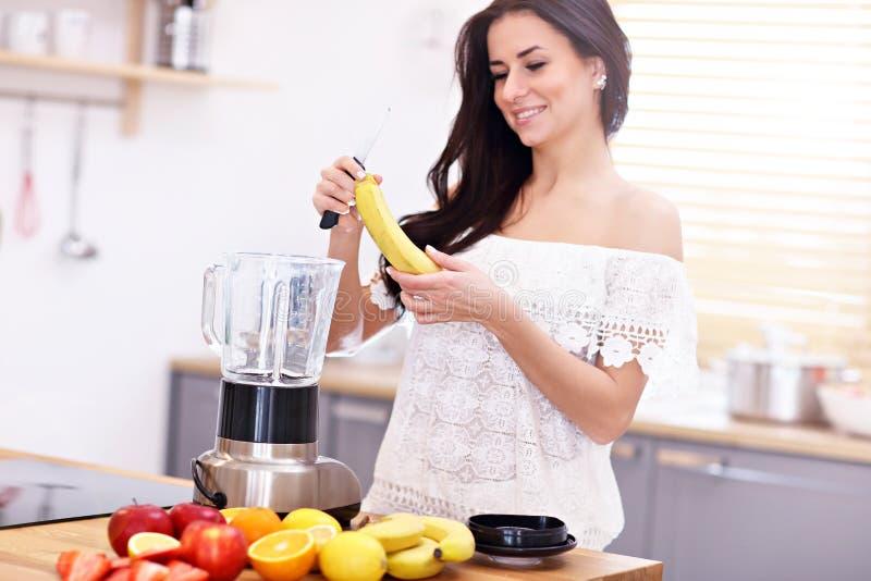 Κατάλληλη χαμογελώντας νέα γυναίκα που προετοιμάζει τον υγιή καταφερτζή στη σύγχρονη κουζίνα στοκ φωτογραφία