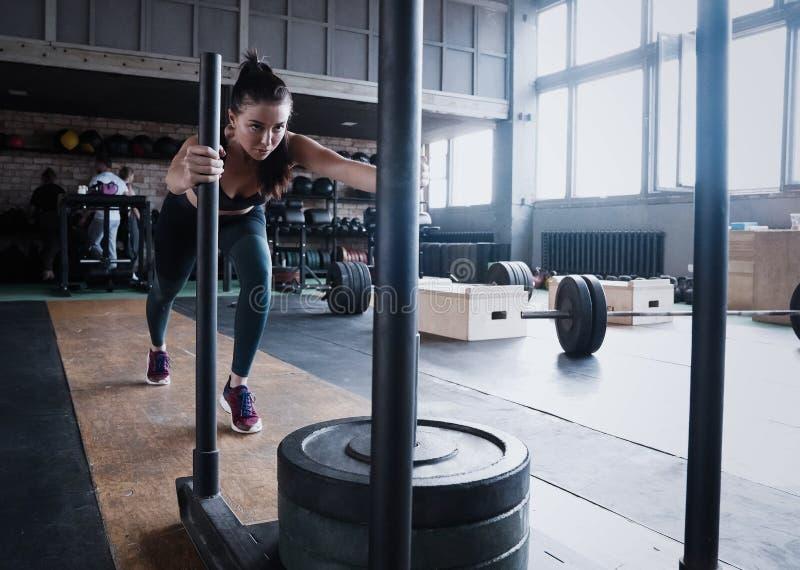 Κατάλληλος θηλυκός αθλητής που επιλύει στη γυμναστική Άσκηση γυναικών Crossfit στοκ εικόνες
