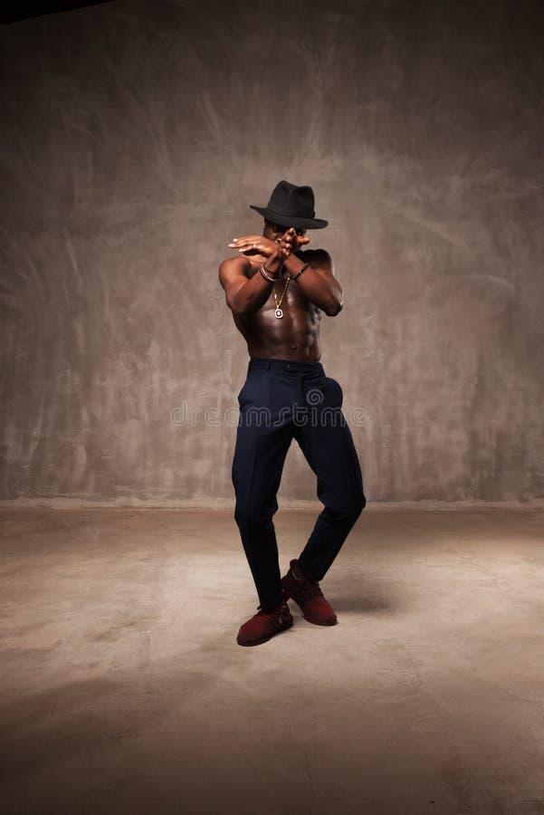 Κατάλληλος ισχυρός νεαρός άνδρας αφροαμερικάνων διάπλασης που φορούν το μαύρο καπέλο και παντελόνι που θέτει το χορό στοκ εικόνα
