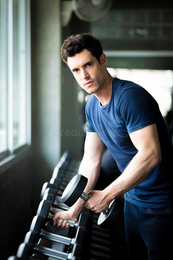 Κατάλληλος καυκάσιος όμορφος νεαρός άνδρας και μεγάλος μυς sportswear Αλτήρας εκμετάλλευσης νεαρών άνδρων κατά τη διάρκεια μιας κ στοκ φωτογραφία