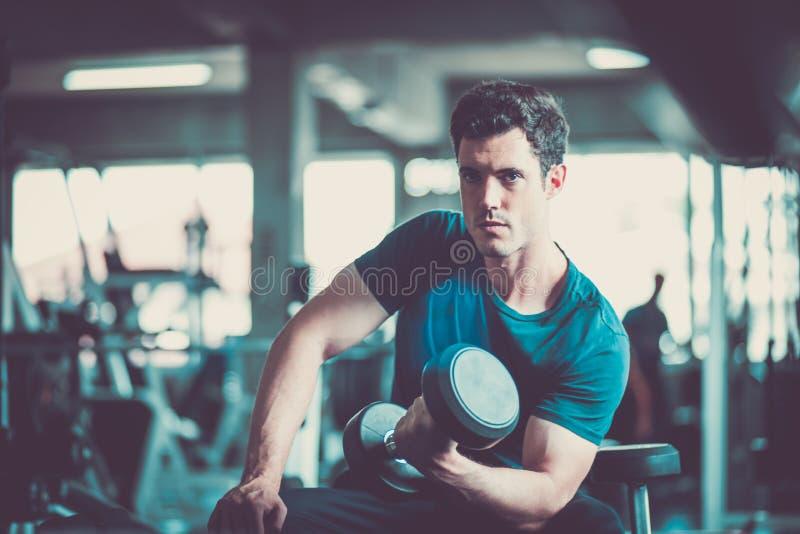 Κατάλληλος καυκάσιος όμορφος νεαρός άνδρας και μεγάλος μυς sportswear Αλτήρας εκμετάλλευσης νεαρών άνδρων κατά τη διάρκεια μιας κ στοκ εικόνα